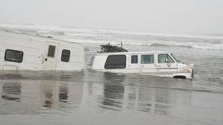 Sand swallows van/trailer after owner parks too close to surfline