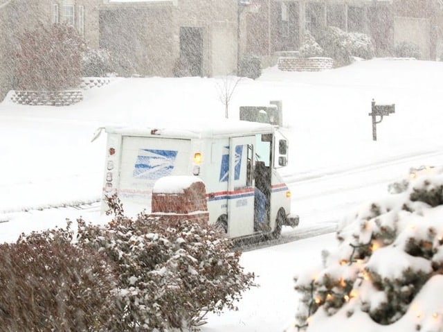 A mail truck and its carrier still delivering the mail in the snow.