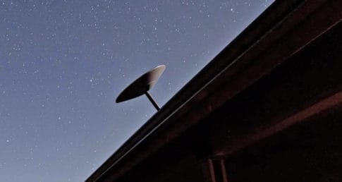 Starlink dish antenna mounted to house